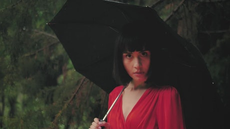 Reverse video of a young woman with umbrella in the rain