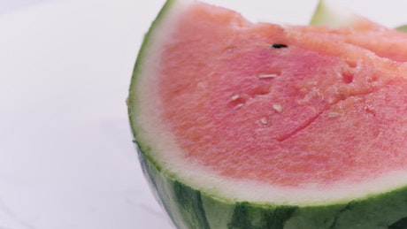 Rich watermelon cut into slices on a white background