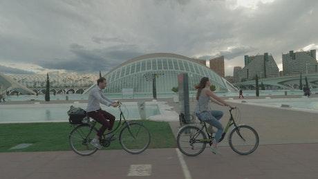 Riding bikes past modern buildings