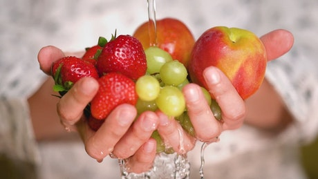 Rinsing strawberries, apples and grapes holding hands