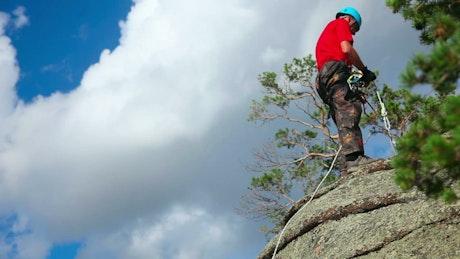 Rock climber descending on rock