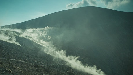Rocky volcano while the smoke covers it
