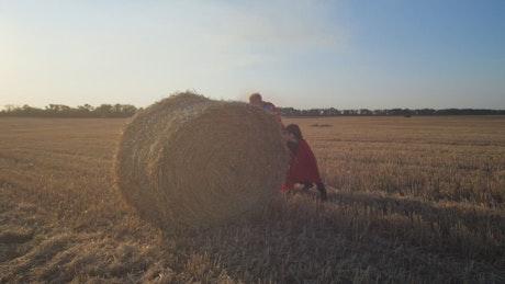 Rolling a huge bale of hay