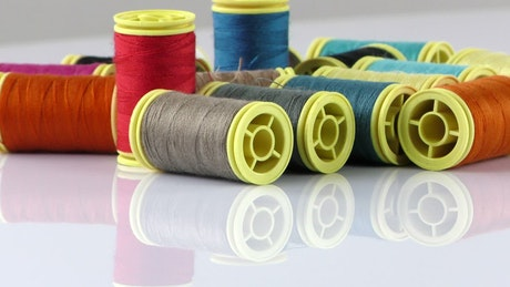 Rolls of thread on a reflective white table