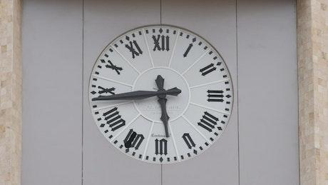 Roman numeral church clock moving fast