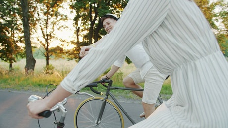 Romantic couple hold hands on country bike ride