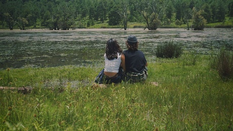 Romantic couple sitting on the shore of a lake