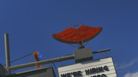 Rotating neon sign of lips on top of a business