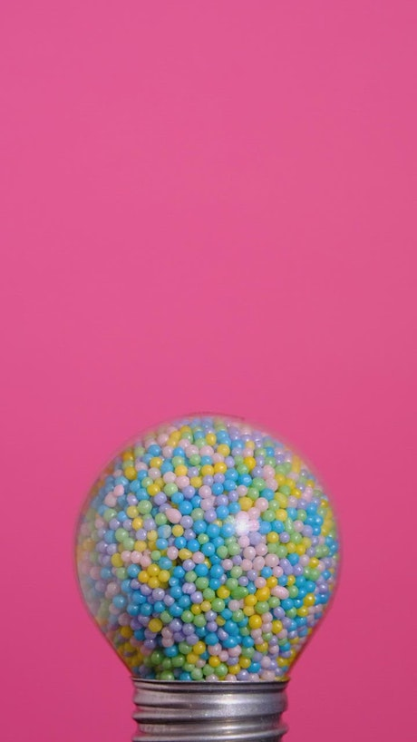 Round spotlight that glows full of colorful candies on a pink background