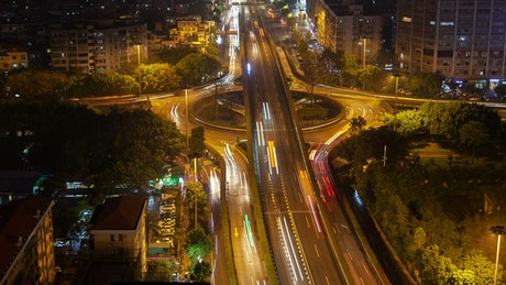 Roundabout and overpass with fast traffic at night