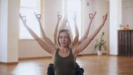 Row of women practicing meditation poses with arms