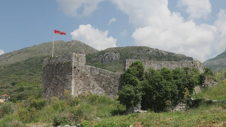 Ruins of an old building with a red flag