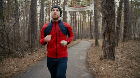 Runner in forest checks heart rate on smartwatch