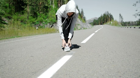 Runner ties laces before starting jog on mountain road