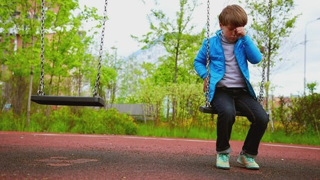 Sad lonely boy sitting on the swings at the playground