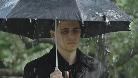 Sad man at a funeral raining with umbrella