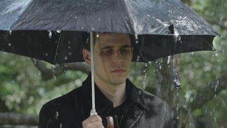 Sad man at a funeral raining with umbrella