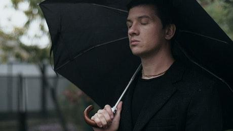 Sad man at a funeral with an umbrella