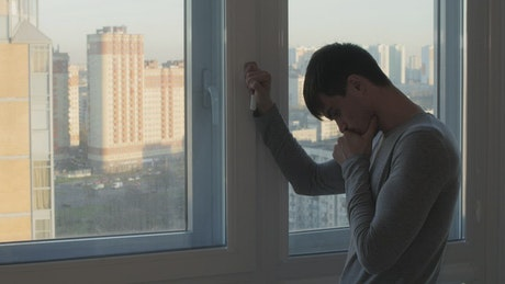 Sad man by his apartment window