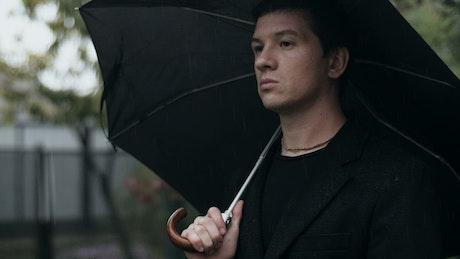 Sad man with an umbrella at a funeral