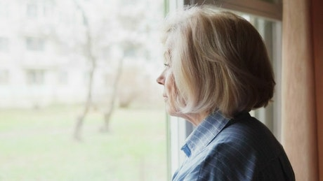 Sad woman looking out of a large window