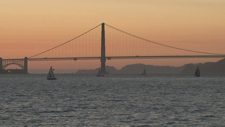 Sailboats in front of the Golden Gate Bridge during sunset