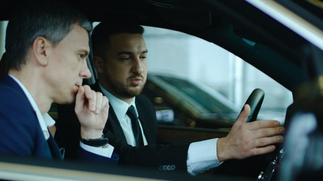 Salesman showing new car to client
