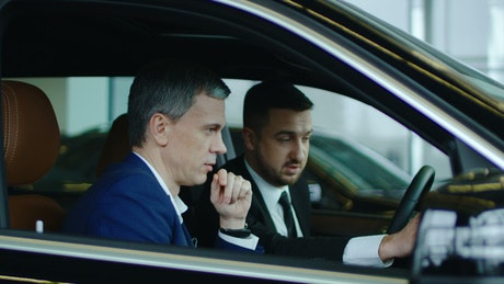 Salesman showing the car to a client
