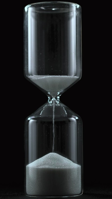 Sand falling from an hourglass on a black background