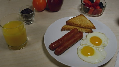 Sausages with egg and fruits