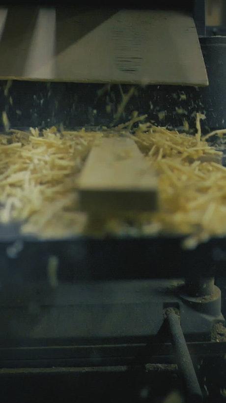 Sawdust falling into a machine in a carpentry