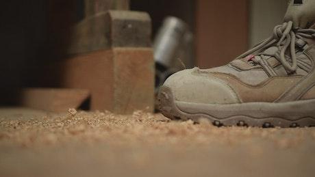 Sawdust falling on a carpenter's feet