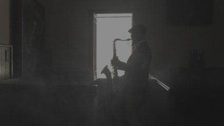 Saxophonist silhouette playing music in a dark room