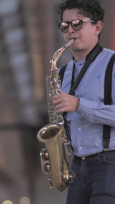 Saxophonist with sunglasses playing on the street
