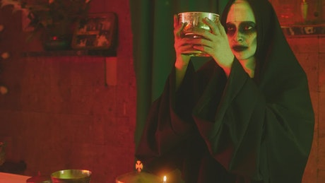 Scary ghost nun lifting a chalice in a church