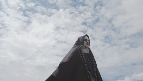 Scary ghost nun outside on a sunny day