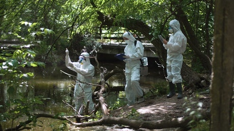 Scientist in biohazard suits collecting samples