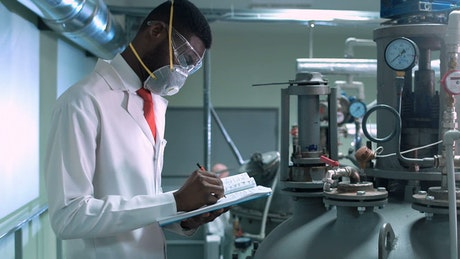 Scientist in facemask writing in a chemical lab