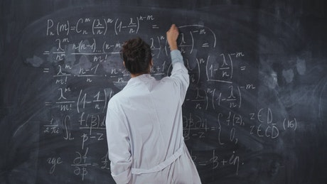 Scientist student solving formulas on a blackboard