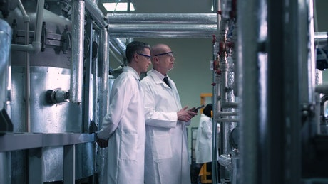 Scientists looking at laboratory pipes
