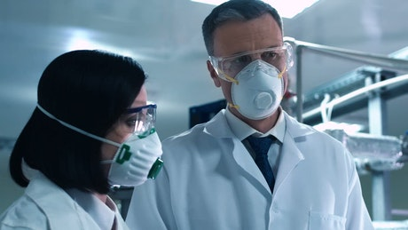 Scientists wearing a face mask talking in the lab