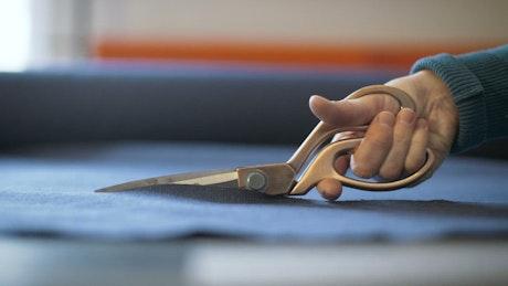 Scissors cutting a blue fabric