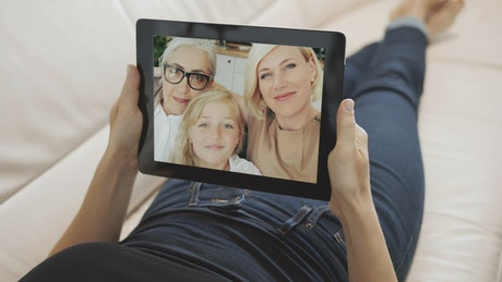 Screen view of family waving hello on tablet
