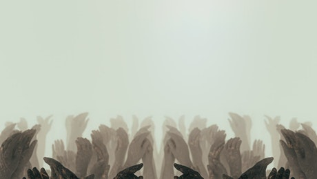 Sculptures of raised hands on a white fog background