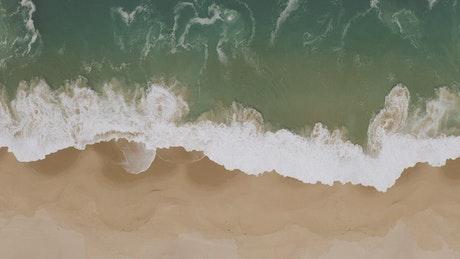 Sea waves hitting the sandy seashore