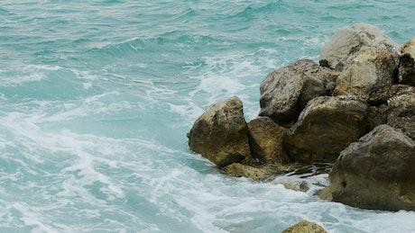 Sea waves reaching a rocky shoreline, close up