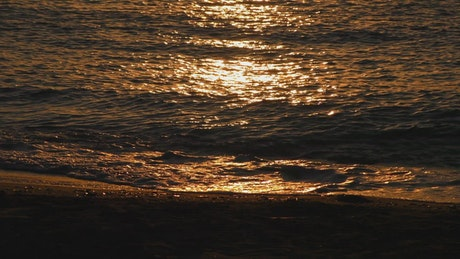 Sea waves reflecting the sunset, close up