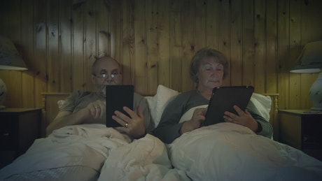 Senior couple reading on the bed with devices