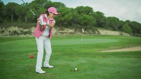 Senior female playing golf