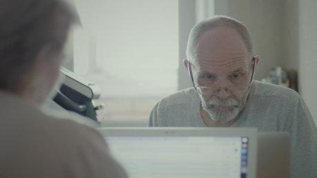 Senior man reading information on the computer